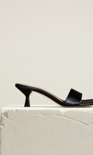 Cove Heel Black , A seamless and supple leather front strap designed to a modern square silhouette. The angled mid-heel adds just the right amount of lift for all day wear. The epitome of modern minimalism, this refined style pairs with everything from denims to dresses and easy workday looks. Made by hand in Italy.