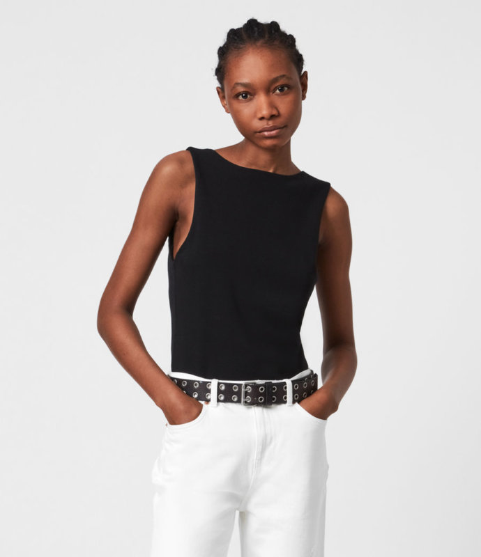 A MODEL WEARING A BLACK BODYSUIT AND WHITE TROUSERS ADVERTISING ALL SAINTS